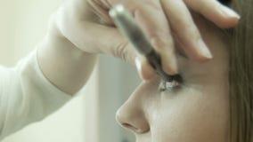 Maquilhador que aplica o lápis de olho na pálpebra vídeos de arquivo