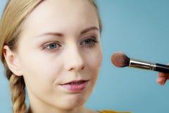 Maquilhador que aplica-se com vermelho da escova na verificação fêmea Fotografia de Stock