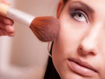Maquilhador que aplica-se com vermelho do pó da escova na verificação fêmea Fotografia de Stock