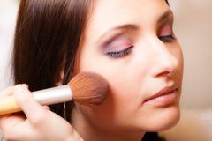 Maquilhador que aplica-se com vermelho do pó da escova na verificação fêmea Imagem de Stock Royalty Free