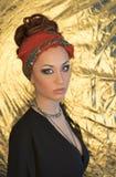 Maquillage Belle femme, dame élégante, style original, fond d'or Brune avec le bandeau rouge Photographie stock