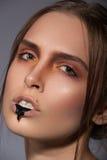 Maquillage créatif de beauté avec le ruissellement noir sur des lèvres Images stock