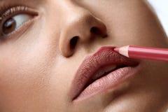 Maquillage de visage Belle femme employant le stylo de lèvre, crayon pour des lèvres Photos libres de droits