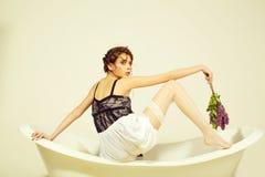 Maquillage femelle femme de pose à la mode jeune femme se reposant dans la baignoire de station thermale avec les cheveux à la mo photos libres de droits