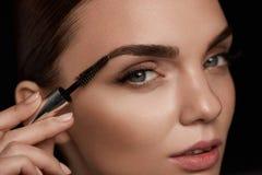 Maquillage parfait pour la belle femme Entretenir de front des sourcils photo stock