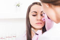 Maquillage permanent pour des sourcils de belle jeune femme dans le salon de beauté images stock