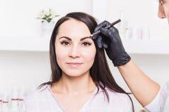 Maquillage permanent pour des sourcils de belle jeune femme dans le salon de beauté photo libre de droits