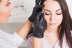 Maquillage permanent pour des sourcils de belle jeune femme dans le salon de beauté photographie stock