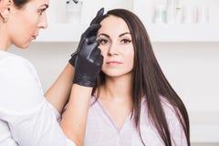 Maquillage permanent pour des sourcils de belle jeune femme dans le salon de beauté photos libres de droits