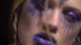 Maquillage pourpre d'une fille qui ouvre son énergie sous forme de troisième oeil, peinture de corps banque de vidéos