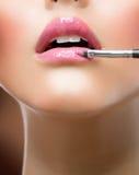 Maquillaje. Aplicación de Lipgloss Fotos de archivo