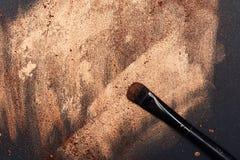 Maquillaje Art Brush en superficie pintada de oro Fotos de archivo