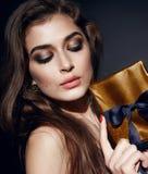 Maquillaje atractivo hermoso de la tarde del brunett de la mujer con el presente de la caja Imagen de archivo libre de regalías