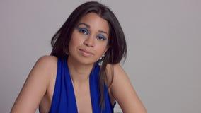 Maquillaje azul del withbright de la mujer joven de la raza mixta en lanzamiento del estudio en vestido azul eléctrico metrajes