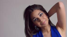 Maquillaje azul del withbright de la mujer joven de la raza mixta en lanzamiento del estudio en vestido azul el?ctrico almacen de video