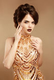Maquillaje de la belleza hairstyle Mujer de la moda en vestido del oro Imagen de archivo