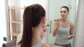 Maquillaje de la cara Mujer que usa el polvo y mirando en espejo almacen de video