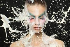 Maquillaje de la fantasía de la muchacha hermosa con el chapoteo de la leche de la cámara lenta Foto de archivo libre de regalías