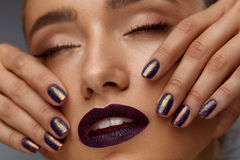 Maquillaje de la manera Mujer hermosa con los labios oscuros y los clavos púrpuras Fotos de archivo libres de regalías