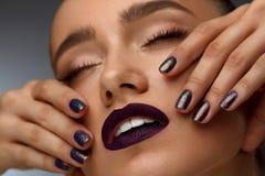 Maquillaje de la manera Mujer hermosa con los labios oscuros y los clavos púrpuras Fotografía de archivo libre de regalías