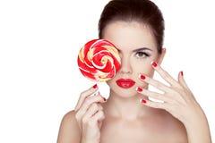 Maquillaje de la moda. Retrato de la muchacha de la belleza que sostiene la piruleta colorida. Imagenes de archivo