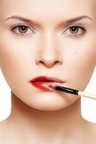 Maquillaje de los labios. Lápiz labial rojo de Applyng usando cepillo del labio Imagen de archivo