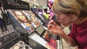 Maquillaje de prueba de la mujer en la tienda de Macys almacen de metraje de vídeo