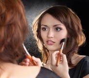 Maquillaje del modelo de manera con el cepillo en el espejo Fotografía de archivo