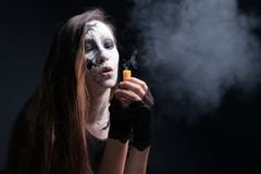 Maquillaje en el estilo de Halloween Una chica joven con el pelo largo con las grietas pintadas en su cara sopló hacia fuera la v imagen de archivo libre de regalías