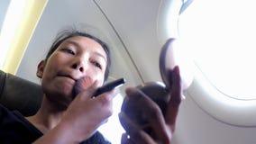 Maquillaje en un avión del vuelo almacen de metraje de vídeo