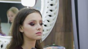 Maquillaje festivo brillante para la morenita con los ojos marrones Cara hermosa Piel perfecta Aplicaci?n de maquillaje almacen de video