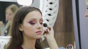 Maquillaje festivo brillante para la morenita con los ojos marrones Cara hermosa Piel perfecta Aplicaci?n de maquillaje almacen de metraje de vídeo