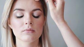 Maquillaje Muchacha hermosa joven que hace maquillaje con el cepillo en mejillas metrajes
