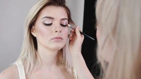 Maquillaje Muchacha hermosa joven que hace maquillaje con el cepillo en mejillas almacen de video
