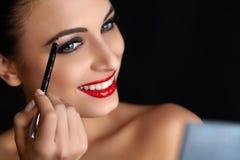 Maquillaje Mujer hermosa que hace maquillaje Lápiz de ceja Labios rojos Imagen de archivo
