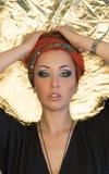 maquillaje Mujer hermosa, señora elegante, estilo original, fondo del oro Morenita con la venda roja Fotografía de archivo libre de regalías