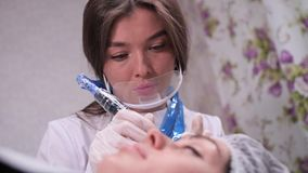 maquillaje permanente de la ceja Un retrato de un cosmetólogo que pinta las cejas de un cliente 4K MES lento almacen de metraje de vídeo