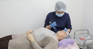 Maquillaje permanente, tatuaje de cejas La aplicación del Cosmetologist compone almacen de metraje de vídeo