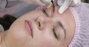 Maquillaje permanente, tatuaje de cejas La aplicaci?n del Cosmetologist compone metrajes
