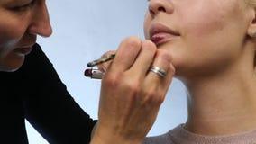 Maquillaje profesional: Lápiz labial rojo en los labios del modelo joven atractivo Cámara lenta metrajes
