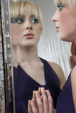 Maquillaje que lleva de la muchacha mientras que mira en espejo Fotografía de archivo libre de regalías