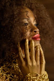 Maquillaje y accesorios serios del oro de la mujer que lleva americana africana o negra que tocan su barbilla con las manos, vist Foto de archivo libre de regalías