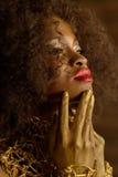 Maquillaje y accesorios serios elegantes del oro de la mujer que lleva americana africana o negra que presentan tocando su barbil Fotografía de archivo