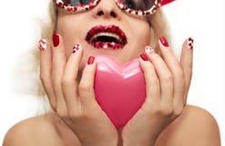 Maquillaje y manicura del día de fiesta con los corazones rojos Foto de archivo