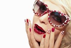 Maquillaje y manicura del día de fiesta con los corazones rojos Fotos de archivo