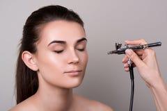 Maquilleur à l'aide de l'aerographe Façonnez le modèle de brune avec la queue de cheveux au-dessus du fond gris Maquillage profes image libre de droits