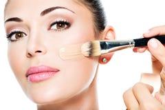 Maquilleur appliquant la base tonale liquide sur le visage Photographie stock