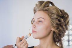 Maquilleur appliquant la base tonale liquide sur le visage de la femme Images libres de droits