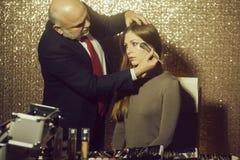 Maquilleur appliquant la poudre avec la brosse sur le visage de femme photographie stock libre de droits