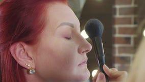 Maquilleur appliquant le crayon correcteur sur le visage modèle du ` s banque de vidéos